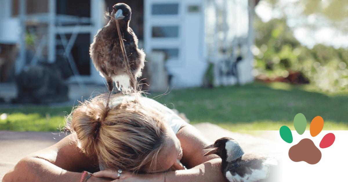 Mit verdecktem Gesicht liegt Sam Bloom bäuchlings auf der Wiese, auf ihrem Kopf und neben ihrem Arm stehen zwei Elstern.